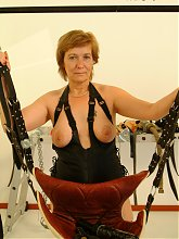 Kinky mature slut in a sexswing in action